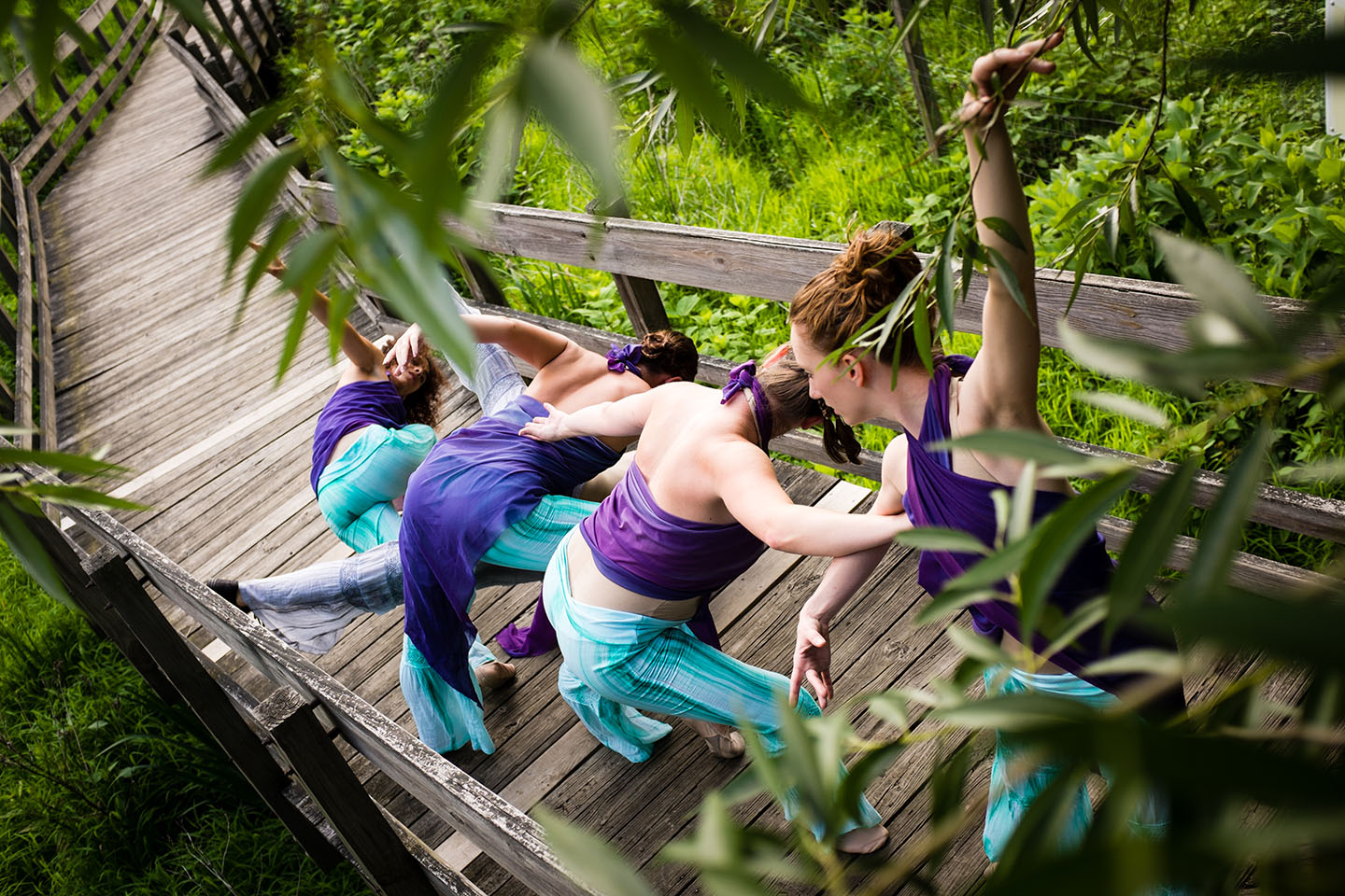 Image of 4 MorrisonDancers dancing down a wooden stairway outdoors in purple costumes
