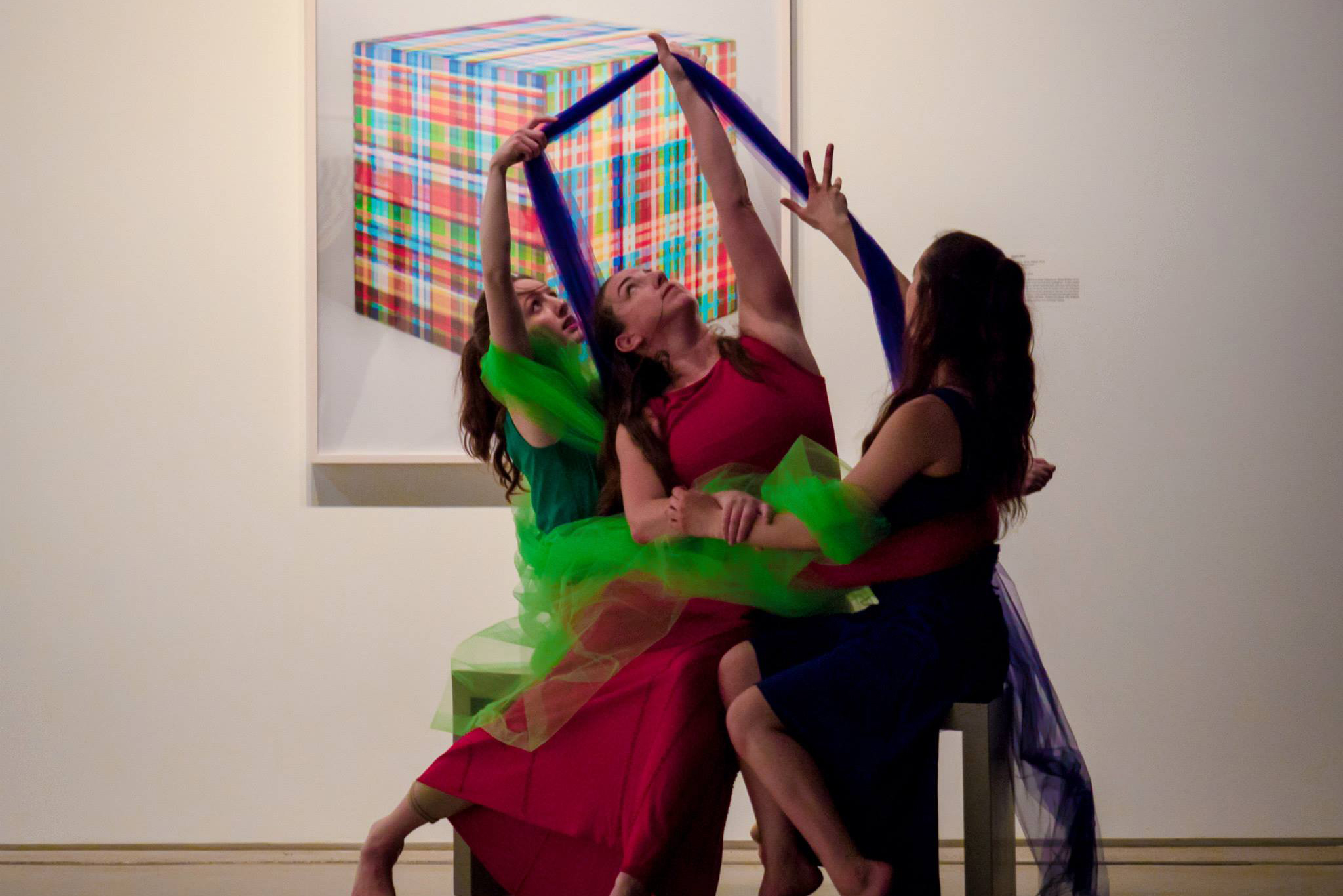Image of 3 MorrisonDancers reaching towards the ceiling wearing red, green, and blue in their RGB performance at the Cleveland Museum of Contemporary Art